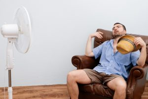 man-feeling-hot-in-front-of-fan