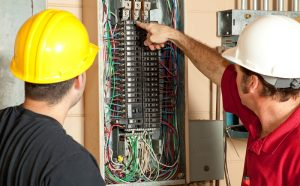 electricians-inspecting-circuit-breaker-panel